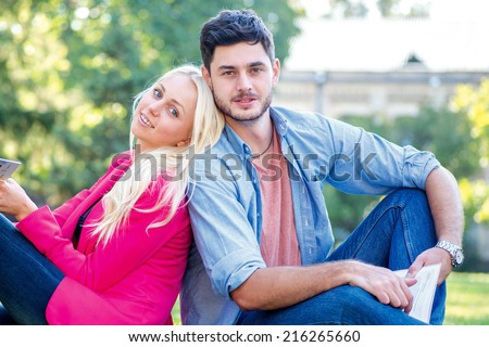Students love. Student girl and boy student holding books and looking at the camera while sitting on the grass near the building of the university on a break. - stock photo
