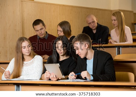 students on lecture in university classroom and look at tablet