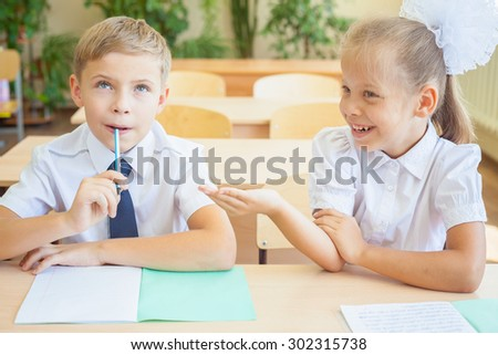 Students or classmates in school classroom sitting together at desk. Schoolboy thought, and girl helps him for the classwork. They are dressed in school uniforms. On table there is notebook and pen. - stock photo