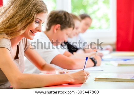 Students or pupils of school class writing an exam test in classroom concentrating on their work - stock photo
