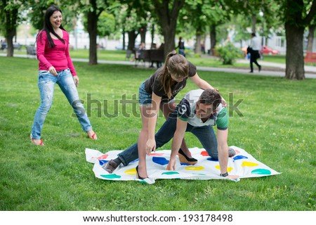 Students play a game in the park twister - stock photo