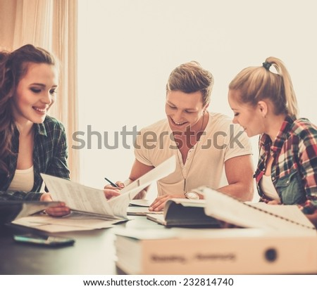 Students preparing for exams in apartment interior behind table  - stock photo