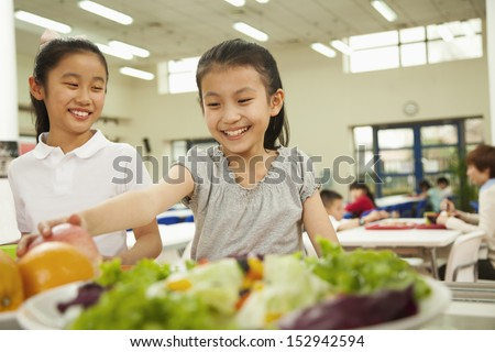 Students reaching for healthy food in school cafeteria - stock photo