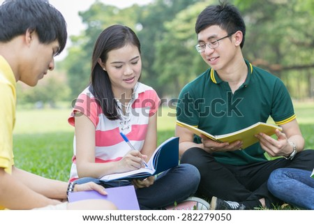 Students reading a book together in the park.