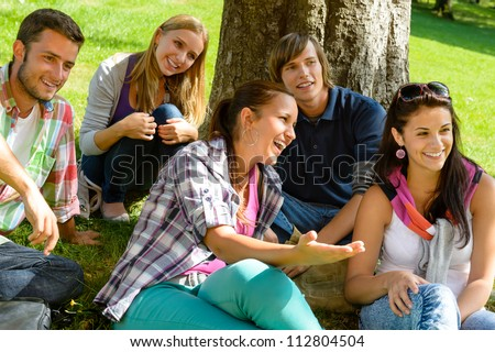Students relaxing in schoolyard teens meadow park laughing campus young - stock photo