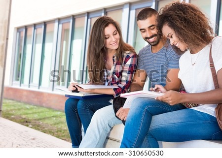 Students sharing notes in the university campus - stock photo