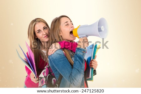 Students shouting by megaphone over ocher background - stock photo
