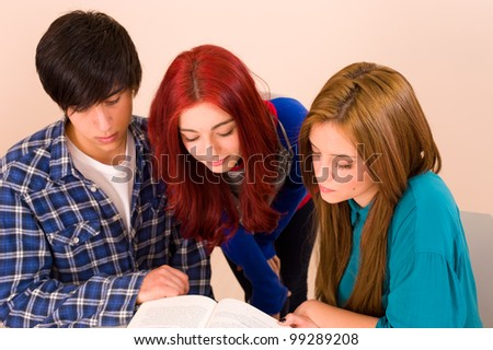 Students showing interest for a book - stock photo
