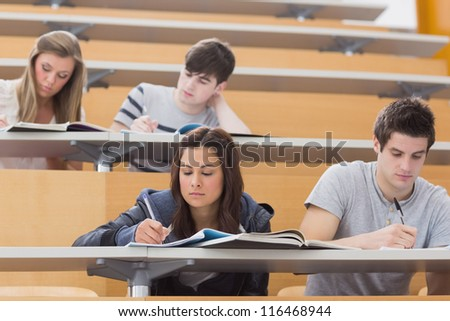 Students sitting at desks in lecture hall taking notes