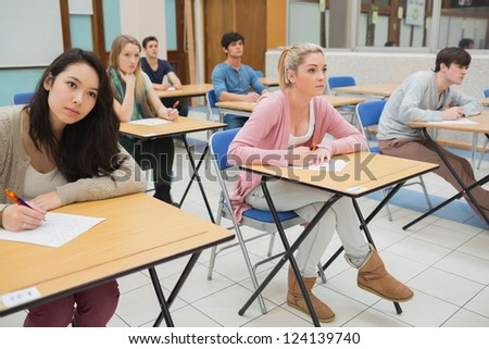 Students sitting at the classroom while writing - stock photo