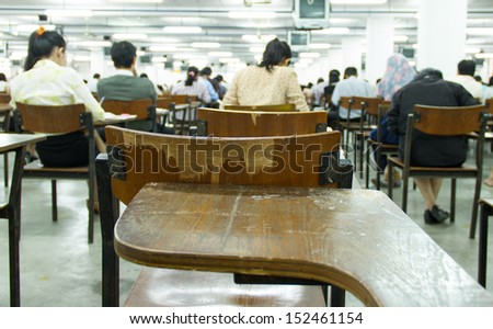 Students sitting in an exam hall doing an exam in university - stock photo
