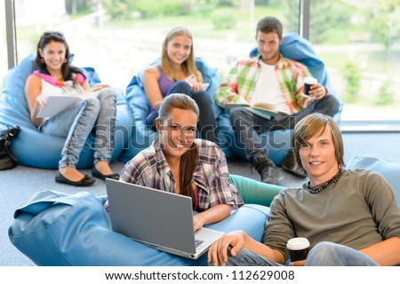 Students sitting on beanbags study room high-school teens happy - stock photo