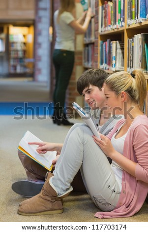 Students sitting on floor of library and studying against book shelf - stock photo