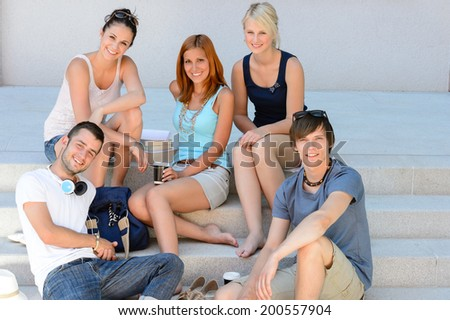 Students sitting on school stairs smiling college friends summer time - stock photo