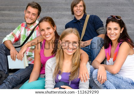 Students sitting on school stairs smiling teens campus college friends - stock photo