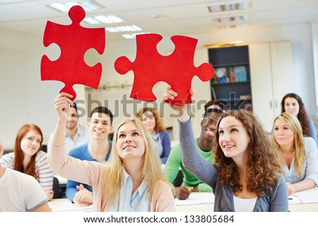 Students solving jigsaw puzzle as a team in university class - stock photo