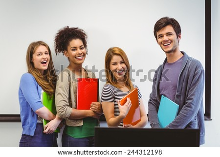 Students standing and smiling at camera holding notepads in classroom