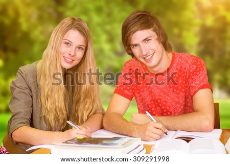 Students studying against trees and meadow - stock photo