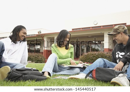 Students studying and sitting on grass