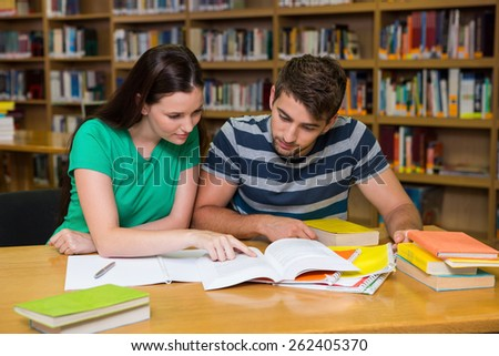 Students studying together in the library at the university - stock photo