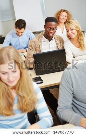 Students studying with laptop computer in class and talking to each other - stock photo