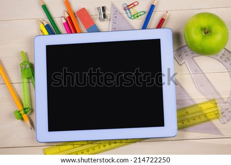 Students table with school supplies and tablet pc - stock photo