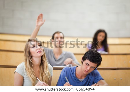 Students taking notes while their classmate is raising his hand in an amphitheater - stock photo