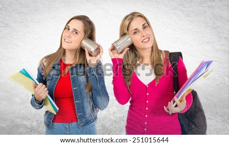 Students talking through a tin phone over textured background - stock photo