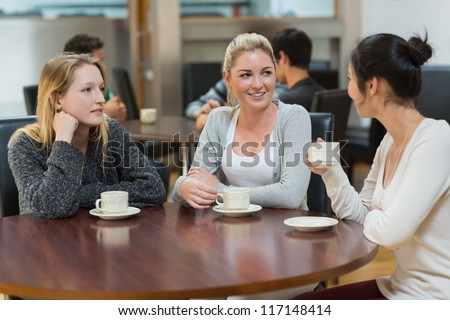 Students talking together in college coffee shop and smiling - stock photo