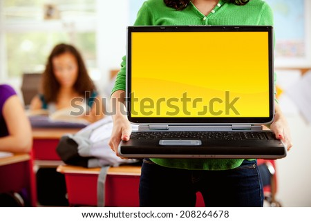 Students: Teen Student Holds Up Laptop With Blank Screen - stock photo