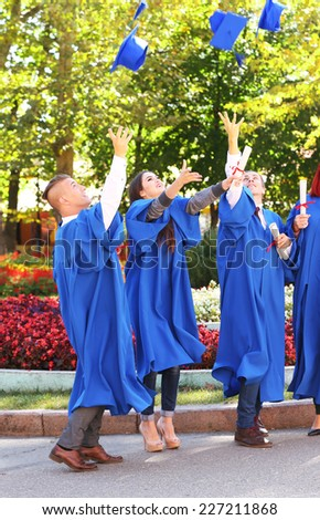 Students throwing graduation hats in air, outdoors - stock photo