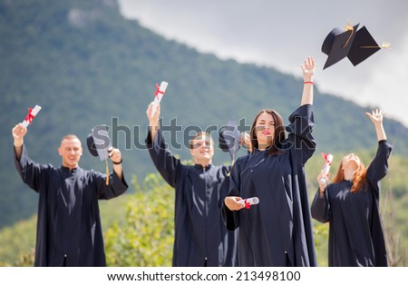 Students throwing graduation hats in the air celebrating - stock photo