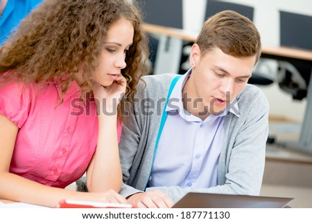students together to discuss the lecture, come together, looking at laptop monitor - stock photo