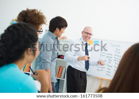 Students trying to guess the English word their teacher keeps in mind while giving a hint - stock photo