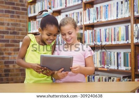 Students using a tablet pc together at the elementary school - stock photo