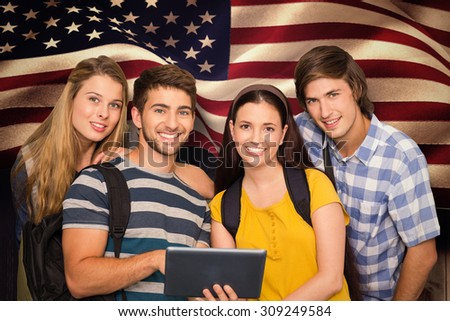 Students using digital tablet at college corridor against composite image of digitally generated united states national flag - stock photo