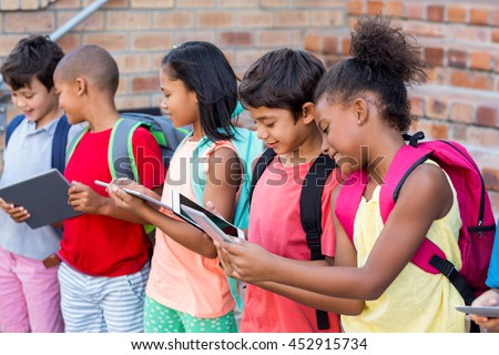 Students using digital tablets outside school - stock photo