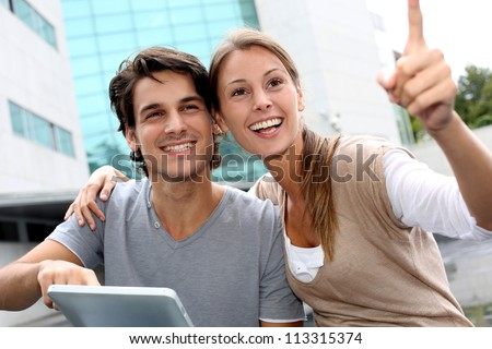 Students using tablet outside and pointing at something - stock photo