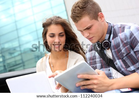 Students using tablet outside university building - stock photo