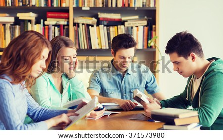 students with books preparing to exam in library - stock photo