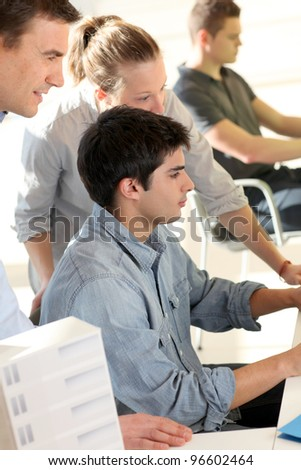 Students with teacher in front of desktop computer - stock photo