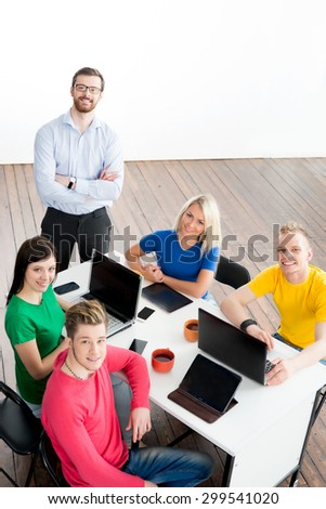 Students with teacher studying using modern technologies. Young startupers have a meeting with a boss. - stock photo