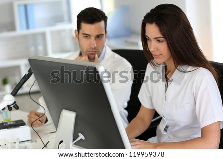 Students working on desktop computer in laboratory - stock photo