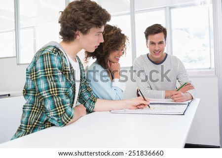 Students working with notebook of pictures at the college