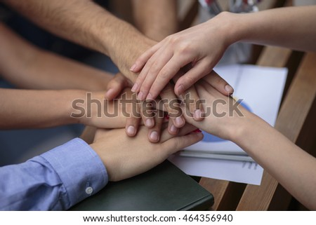 students, young businessmen conclude the deal. hands on background wooden table. shaking hands. Against the background of the table is the coffee, notepad, economic graph.Team
