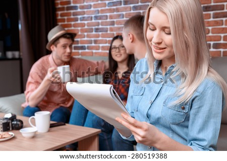 Studentship. Beautiful blond girl drawing in her notebook while her friends sitting on the background talking and drinking coffee in a cafe  - stock photo