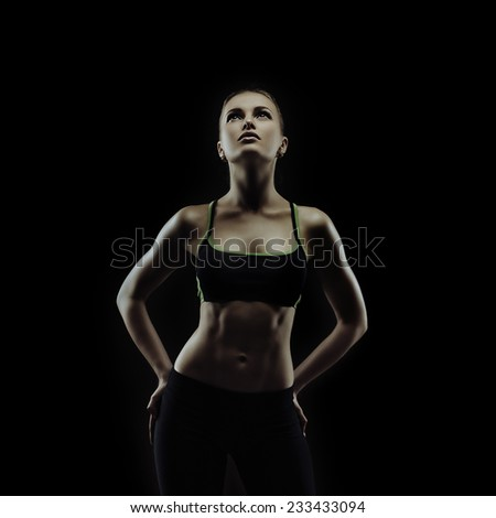 Studio artistic portrait of young fit woman on black