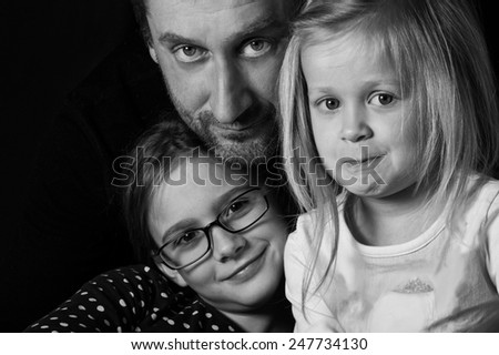 Studio black and white portrait of father and two beautiful daughters, togetherness concept - stock photo