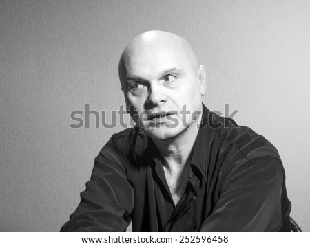 Studio black and white portrait portrait caucasian bald men. Emotions. Pensively looks aside - stock photo
