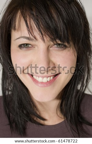 Studio close up portrait of a beautiful young woman with a big cheesy smile. - stock photo